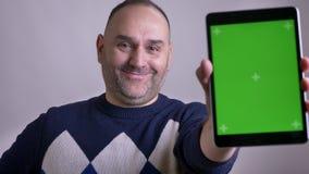 Всход крупного плана середины постарел кавказский мужчина используя планшет и показывать зеленому chroma ключевой экран с объявле акции видеоматериалы