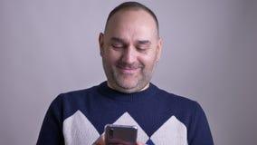 Всход крупного плана середины постарел кавказский мужчина просматривая по телефону смотря камеру и усмехаясь жизнерадостно акции видеоматериалы