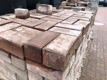 Вымощая каменная красная плитка цемента для класть строительство дорог, мостовую на деревянных паллетах на строительной площадке стоковое фото