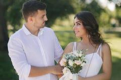 Выхольте и невеста в их дне свадьбы идя в парк Новобрачные тратят время совместно как раз поженено стоковая фотография rf