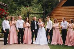Выхольте и стойка невесты с groomsman и bridesmaid снаружи Новобрачные целуя и хлоп друга венчание сбора винограда дня пар одежды стоковые фотографии rf
