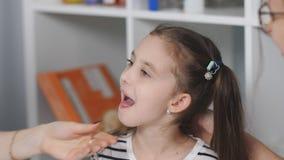 Врач женщины рассматривает боль в горле для пациента маленькой девочки Мать и молодая дочь на приеме на сток-видео
