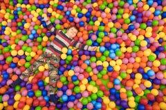 Время траты ребенка в бассейне заполнило с шариками Крытая деятельность Часы досуга для детей ребенк играет с стоковое фото rf