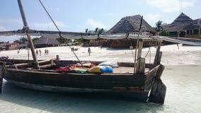 В деревне Nungwi на севере острова Занзибара, рыболовы предлагают задвижку, пока ресторан на пляже добросердечно стоковое фото rf