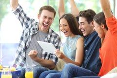 Возбужденная группа в составе друзья наблюдая средства массовой информации на планшете дома стоковые изображения