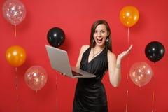 Возбужденная маленькая девочка в меньших руках черного платья распространяя, работая на компьютере ПК ноутбука пока празднующ на  стоковая фотография rf