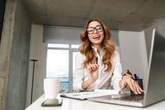 Возбужденная молодая бизнес-леди одетая в официальной рубашке одежд внутри помещения используя ноутбук стоковые изображения
