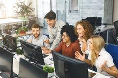 Возбужденные студенты читая хорошие новости совместно на экране компьютера стоковое изображение