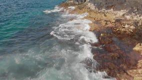 Воздушная съемка Прибой, волны брызгая синь и бирюзу и вулканическую высушенную береговую линию камней и окаменеванный видеоматериал