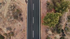 Воздушная съемка Смотреть вниз Автомобили идут новая идеально плоская дорога асфальта Свежие белые дорожные разметки На фоне сток-видео