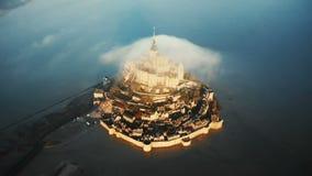 Воздушный взгляд сверху, трутень поднимая над замком острова Мишеля Святого Mont восхода солнца с большим облаком над ним в Норма акции видеоматериалы