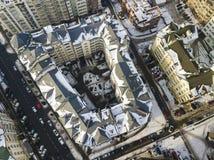 Воздушный черно-белый взгляд сверху зимы современного центра города с высотными зданиями и припаркованными автомобилями на снежны стоковая фотография