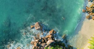 Волны вида с воздуха ломают на пляже острова на заходе солнца Волны моря на красивом пляже трутня 4k Anse Лациа вида с воздуха ос сток-видео