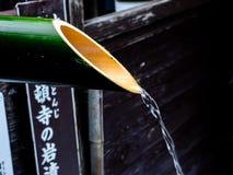 Вода от бамбукового конца трубы вверх стоковые фото