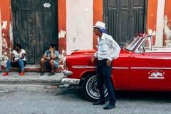 Водитель ждет его клиентов его классическим автомобилем в Гаване, Кубе стоковые изображения rf