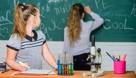 Воспитательная концепция эксперимента Одноклассники девушек изучают химию Микроскоп и пробирки на таблице химические реакции стоковая фотография rf