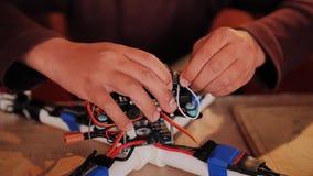 Гай собирает quadrocopter от запасных частей и дизайнера Вентиляторы инженерства радио