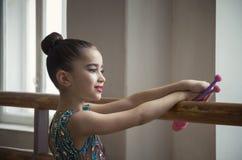 Гимнаст маленькой девочки с клубами смотрит через большое окно в зале для horeography стоковое изображение
