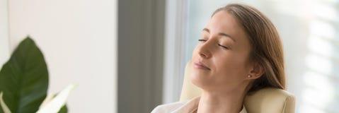 Глаза горизонтальной молодой женщины изображения закрывая отдыхая усаживание на стуле стоковая фотография rf