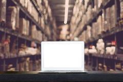 Глумитесь вверх современных компьютера или ноутбука с пустым экраном на таблице с запачканными коробками на строках полок в склад стоковое фото