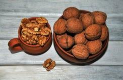 Грецкие орехи, гайки в гончарне, который слезли и unpeeled на белой таблице стоковые фотографии rf