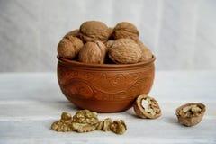 Грецкие орехи, гайки в гончарне на белой таблице стоковое изображение rf