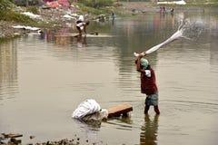 Грязная прачечная: Washerman моет одежды в загрязненной воде стоковые фото
