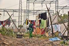Грязная прачечная: Washerman моет одежды в загрязненной воде стоковая фотография