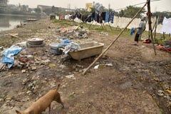 Грязная прачечная: Washerman моет одежды в загрязненной воде стоковая фотография rf