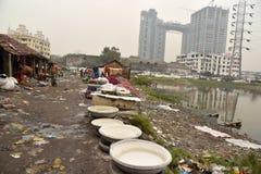 Грязная прачечная: Washerman моет одежды в загрязненной воде стоковое изображение rf