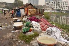 Грязная прачечная: Washerman моет одежды в загрязненной воде стоковое фото rf