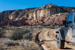 Грязный корабль привода на четыре колеса на изгибать грязную улицу возглавляя к красочной мезе в высоком ландшафте пустыни стоковое фото