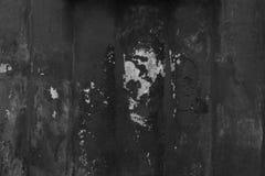 Грубая черная покрашенная бетонная стена с отказами и обломоками в гипсолите стоковое фото rf