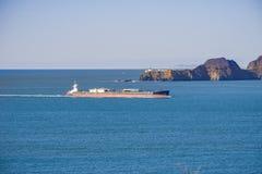 Грузовой корабль подготавливая войти San Francisco Bay; на заднем плане маяк Bonita пункта, Калифорния стоковое фото rf