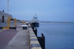 Грузовой корабль связанный для дока на морском порте, опрокидывает вверх, широкоформатный взгляд, солнечный день, голубое небо Ве стоковое фото rf