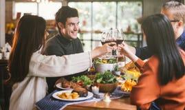 Группа в составе молодые люди наслаждаясь обедающим совместно Обедать концепция партии приветственных восклицаний вина стоковое фото