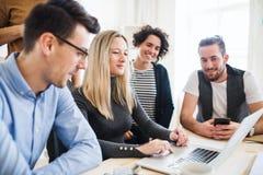 Группа в составе молодые предприниматели с деятельностью ноутбука совместно в современном офисе стоковые изображения rf