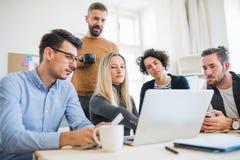 Группа в составе молодые предприниматели с деятельностью ноутбука совместно в современном офисе стоковое фото rf