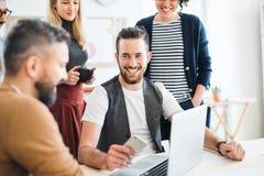 Группа в составе молодые предприниматели с деятельностью ноутбука совместно в современном офисе стоковая фотография