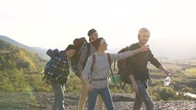 Группа в составе счастливые кавказские люди идя на горы, говоря и усмехаясь молодые людей и туристов женщин на каникулах на видеоматериал