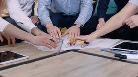 Группа людей работая с чертежи в офисе, правильные неточности Руки на конце-вверх таблицы видеоматериал