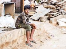 Грустный, сиротливый предназначенный для подростков азиатский мальчик полагаясь в плохой деревне стоковое фото