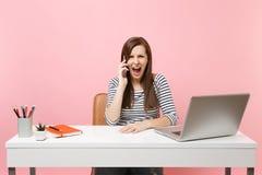 Говорить молодой сердитой женщины кричащий на мобильном телефоне пока сидящ и работающ на проекте на офисе с ноутбуком ПК стоковое изображение rf