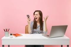 Говорить рук молодой агрессивной женщины распространяя кричащий на промежутке времени мобильного телефона сидит работа на офисе с стоковое изображение rf