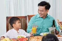 Говоря взрослый человек с ребенк на обедающем семьи стоковые изображения