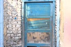 Голубая деревянная дверь в каменной стене получившегося отказ розового дома стоковые фото