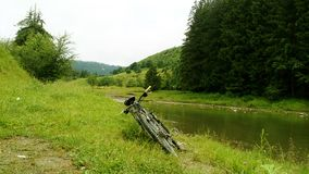Горный велосипед около небольшого реки в горах стоковое изображение