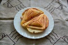 Горячий хрустящий сэндвич Свежий горячий хрустящий очень вкусный тостер на белой плите на завтрак стоковые фото