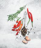 Горохи перца в ложке с частями красного перца, розмаринового масла и чеснока стоковые фотографии rf