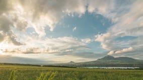 Естественное timelapse захода солнца лета над полями, озером и горами Облака быстро изменяют форму в лучах заходящего солнца сток-видео